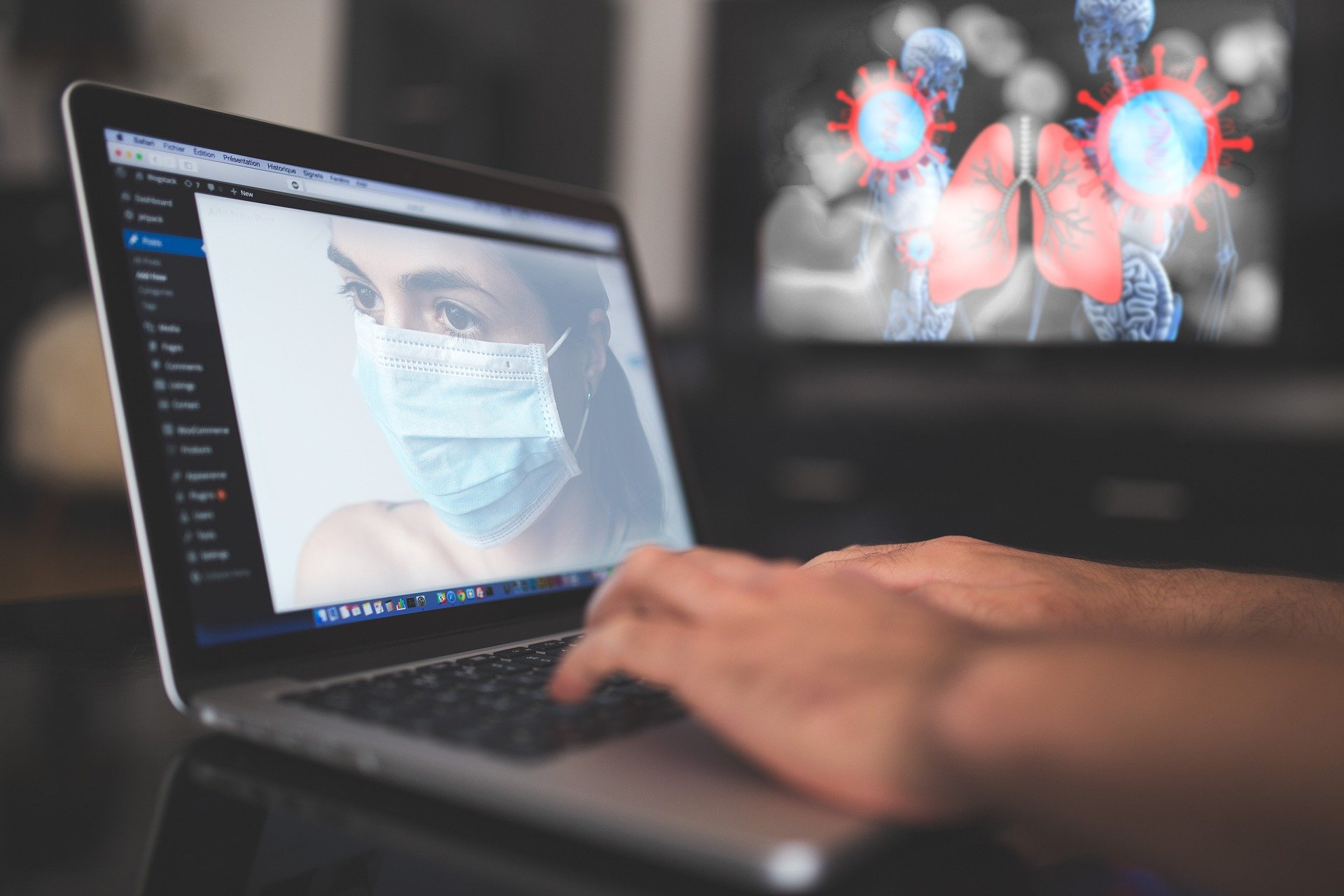 Laptop showing image of woman in a surgical mask