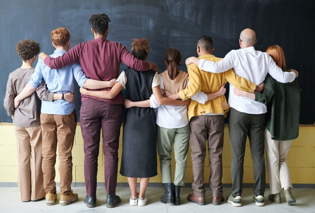 Group of people standing in front of a blackboard