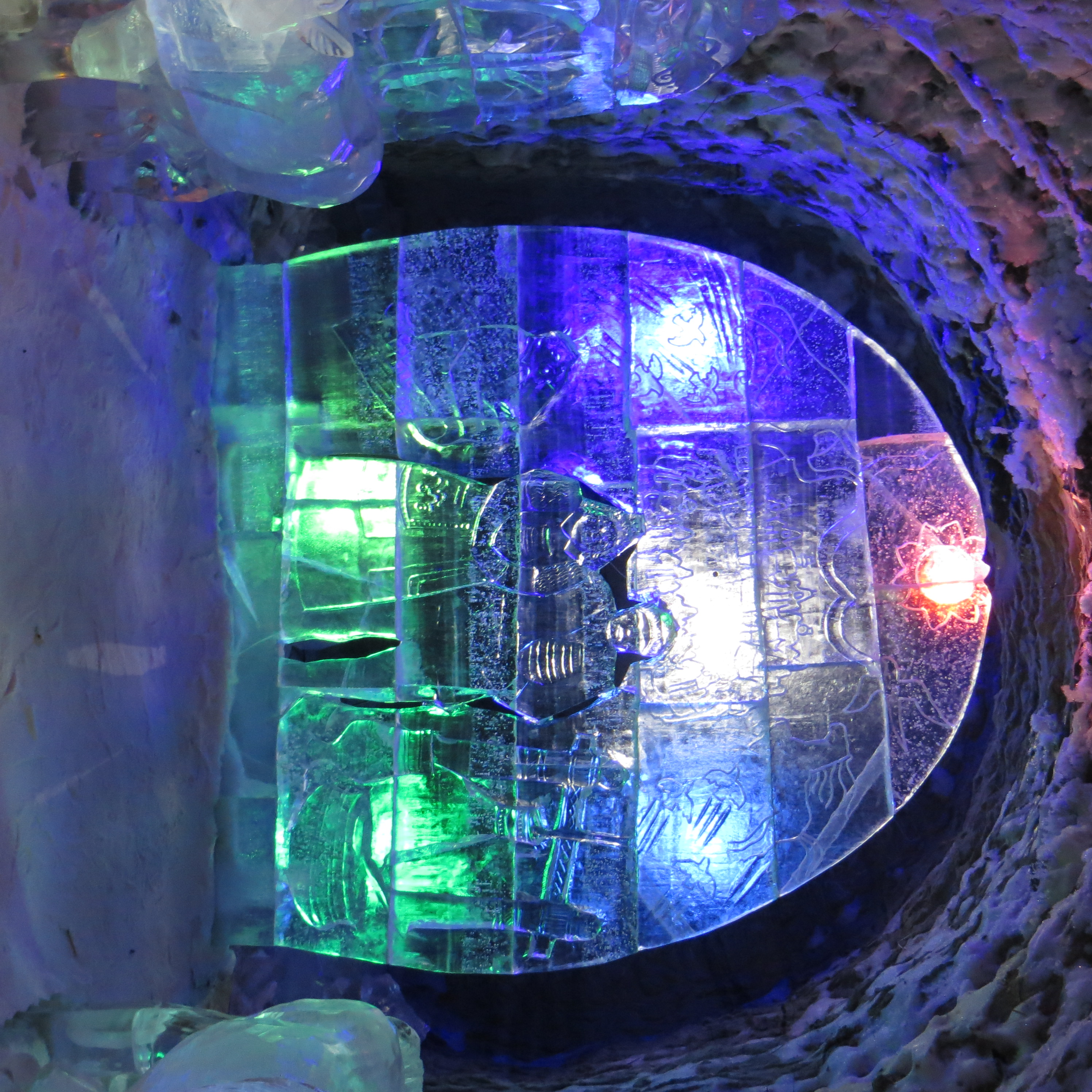 An arch-shaped ice sculpture with patterned engravings. Most prominently depicted are two figures. The sculpture sits in a tunnel with snow on the ceiling and on the ground. There are coloured lights in blue, red and green shining through from behind the ice sculpture.
