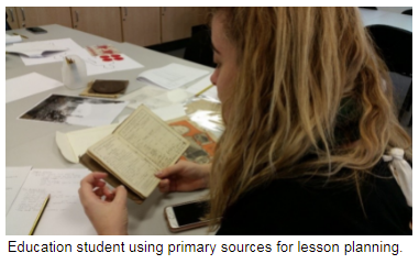 Education student looking at a primary source, a book as part of lesson planning.