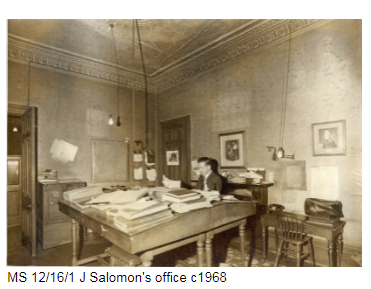 Man sitting behind a large wooden desk, the office of J. Salomon c 1968.