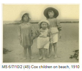 Three children standing on a beach in 1910 wearing protective hats