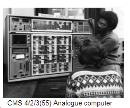 Two people looking at an analogue computer