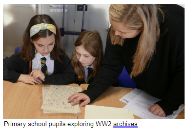 Primary school pupils looking at WW2 archives