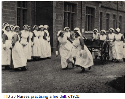 Nurses practising a fire drill c1920. Wearing uniforms with long aprons and hats, some of the nurses are pulling a cart with fire hoses.