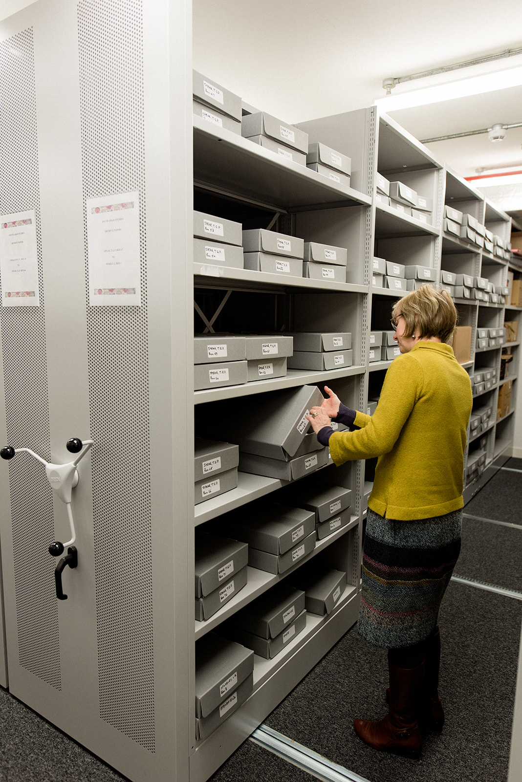 Archivist in storage area inspecting archive boxes