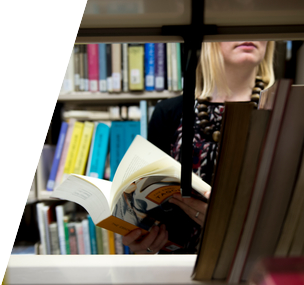 View through bookshelf of a student holding a book