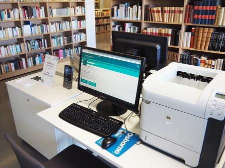 Feeniks-kirjaston kulttuuriaineistojen työaseman tietokone ja tulostin.