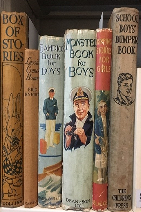 Selection of children's literature books on a shelf including Lassie Comes Home and Monster Book for Boys, among others