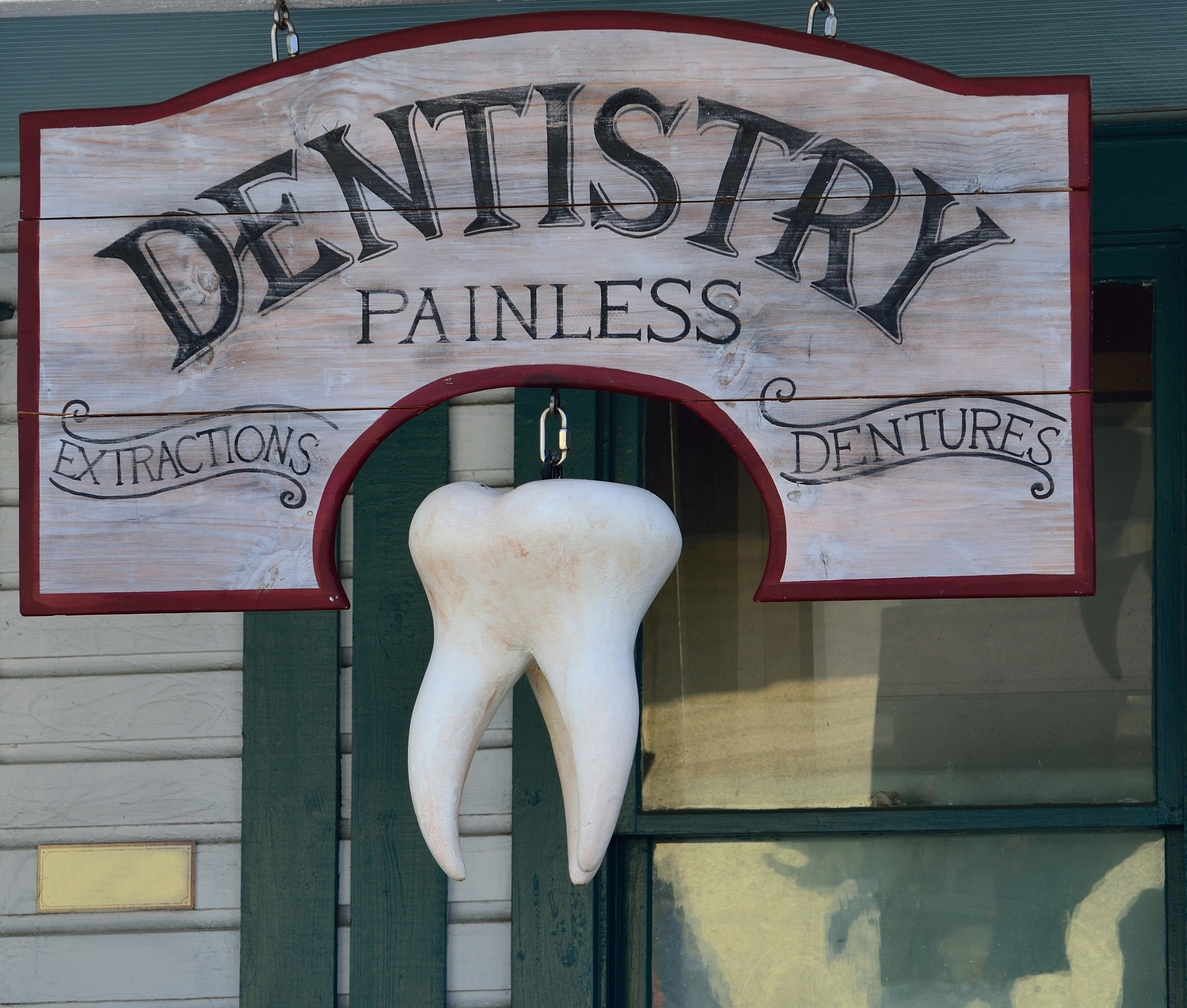 "Sign outside older dentistry booth - ""painless dentistry: extractions, dentures"""