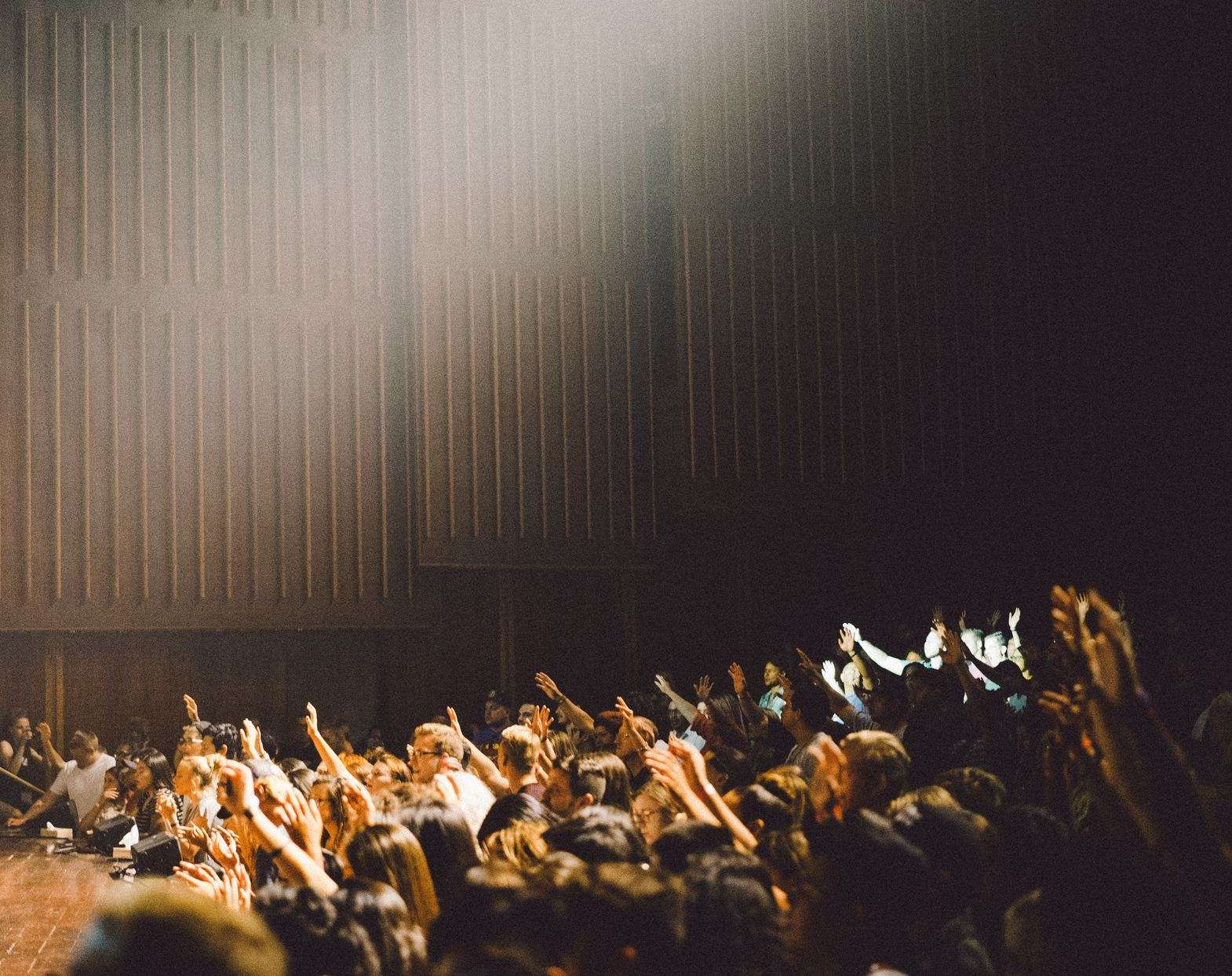 Photograph of a crowd of people in front of a stage.  Some with hands in the air.
