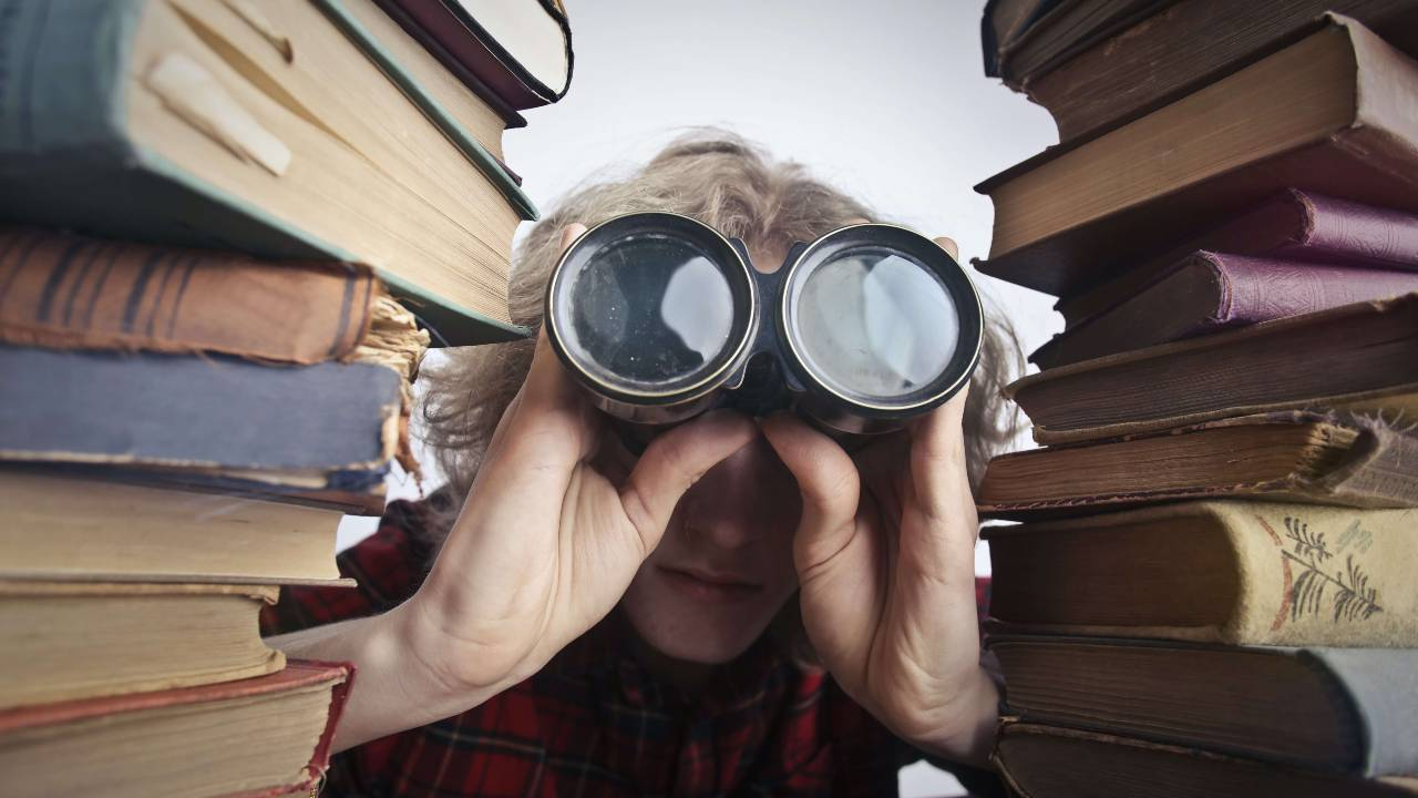 Person searching for books with binoculars