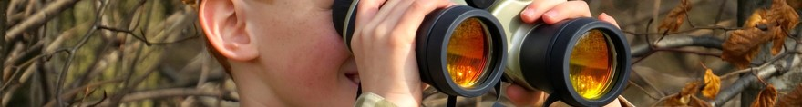 An image of a boy using binoculars.