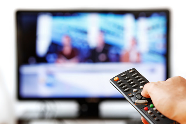 A hand pointing a remote control at a TV displaying a panel show