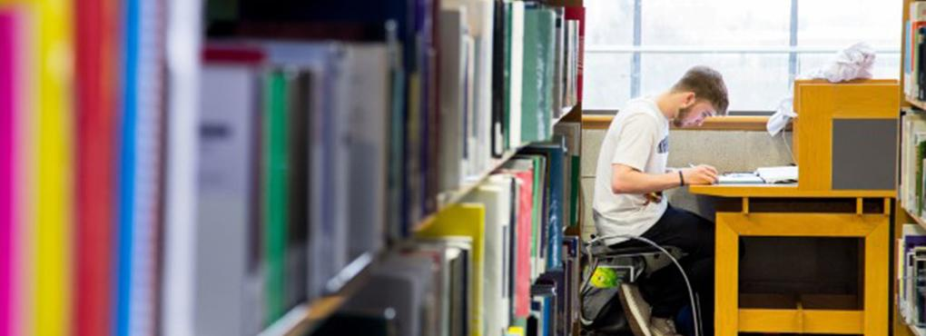 Image of books shelves in the UL Library and student studying