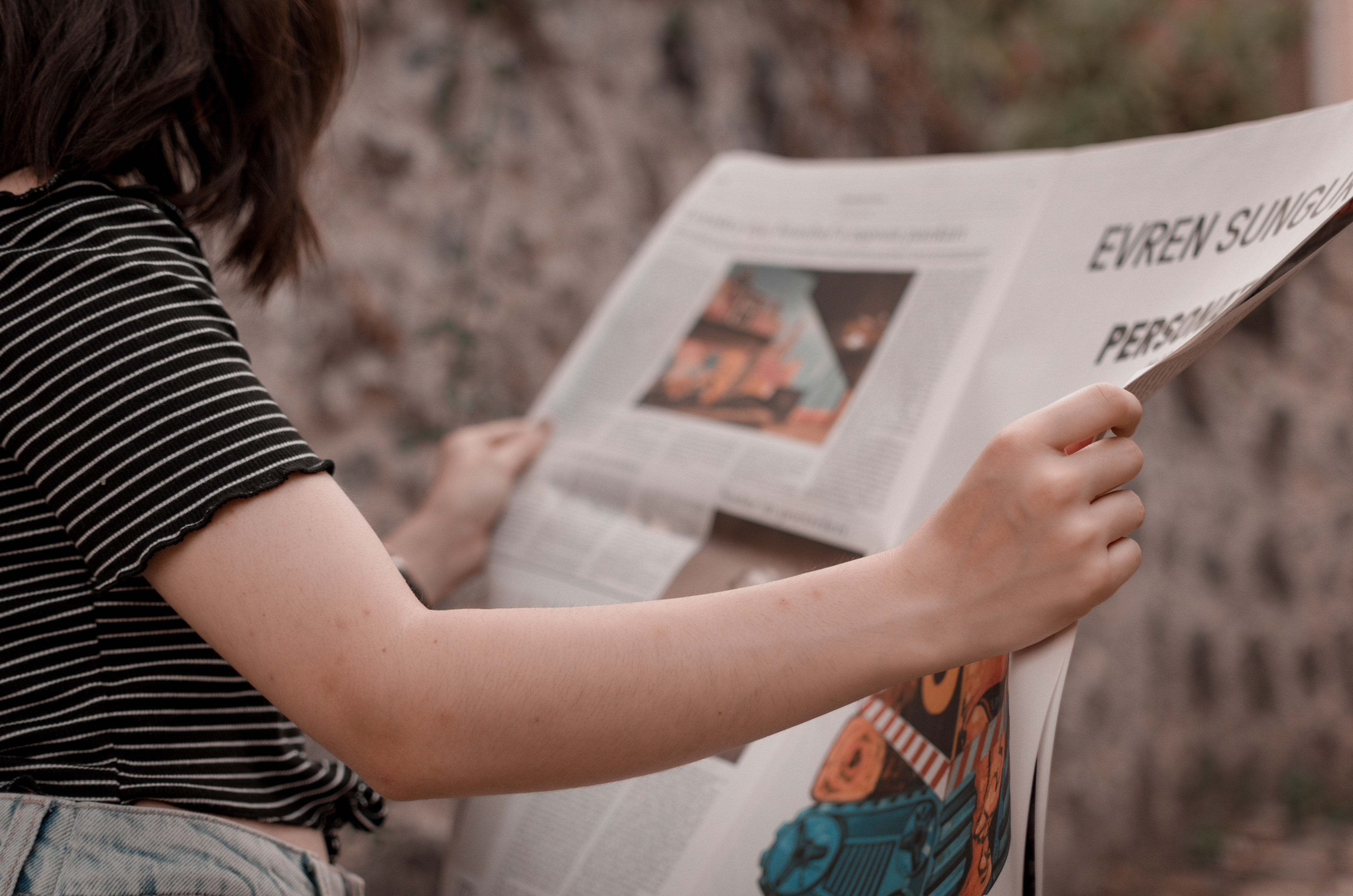 Nainen lukee sanomalehteä.