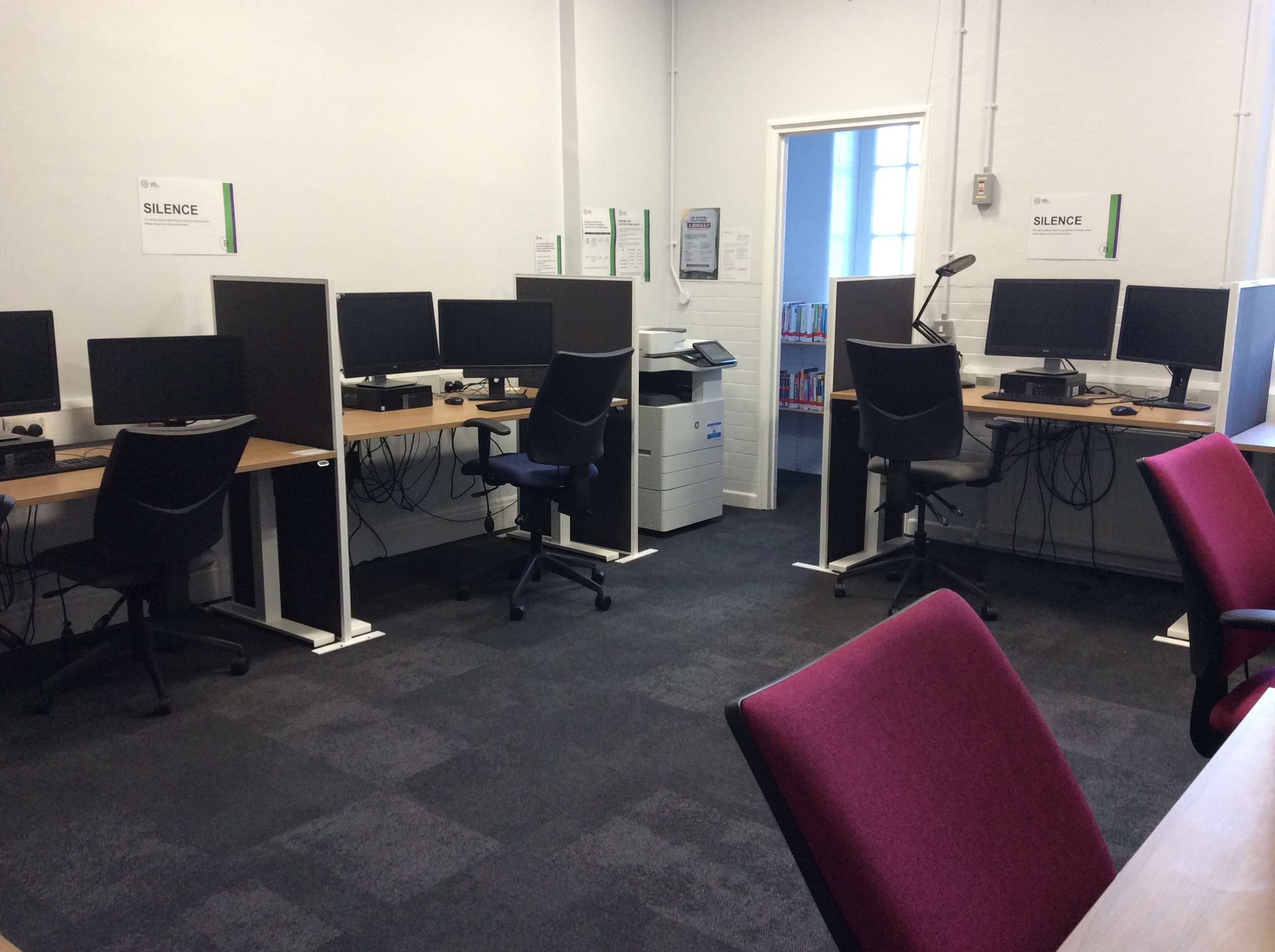 The Disability Resource Area at Sheila Silver Library has a calm and minimalist feel. There are several PCs separated by desk dividers. There is a printer in the corner and a collection of books through a doorway at the back.