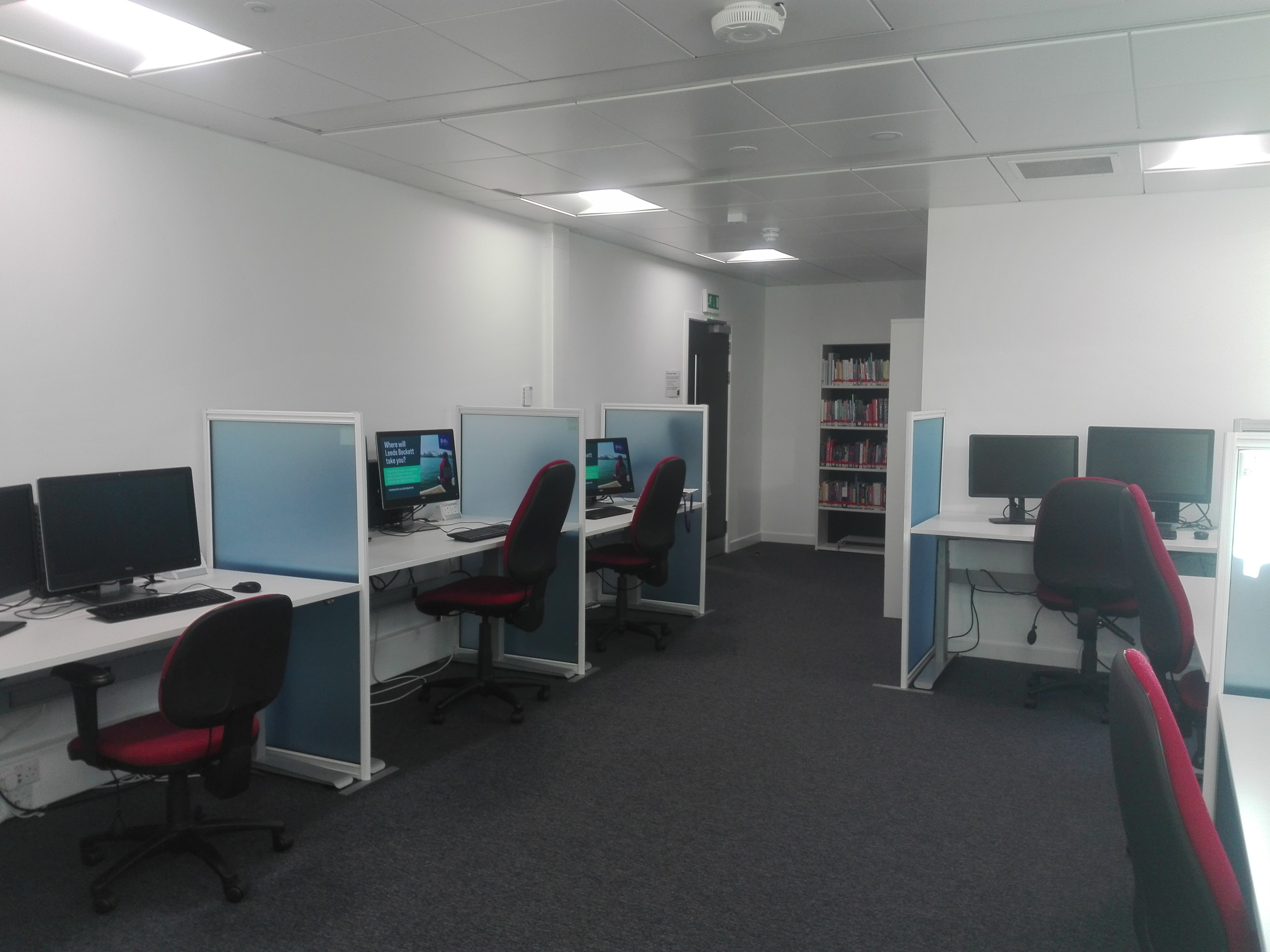 The Disability Resource Area at Sheila Silver Library has a calm and minimalist feel. There are several PCs separated by desk dividers. There is a collection of books by the door.