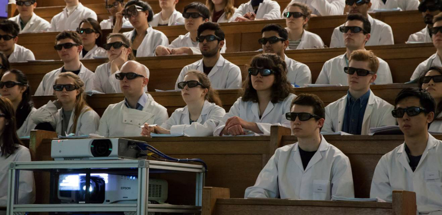 Rows of students in a old fashioned lecture theatre looking at a screen while wearing large 3D sunglasses