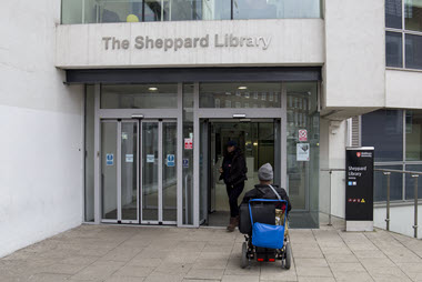 Wheelchair user entering Sheppard Library through the front folding automatic doors