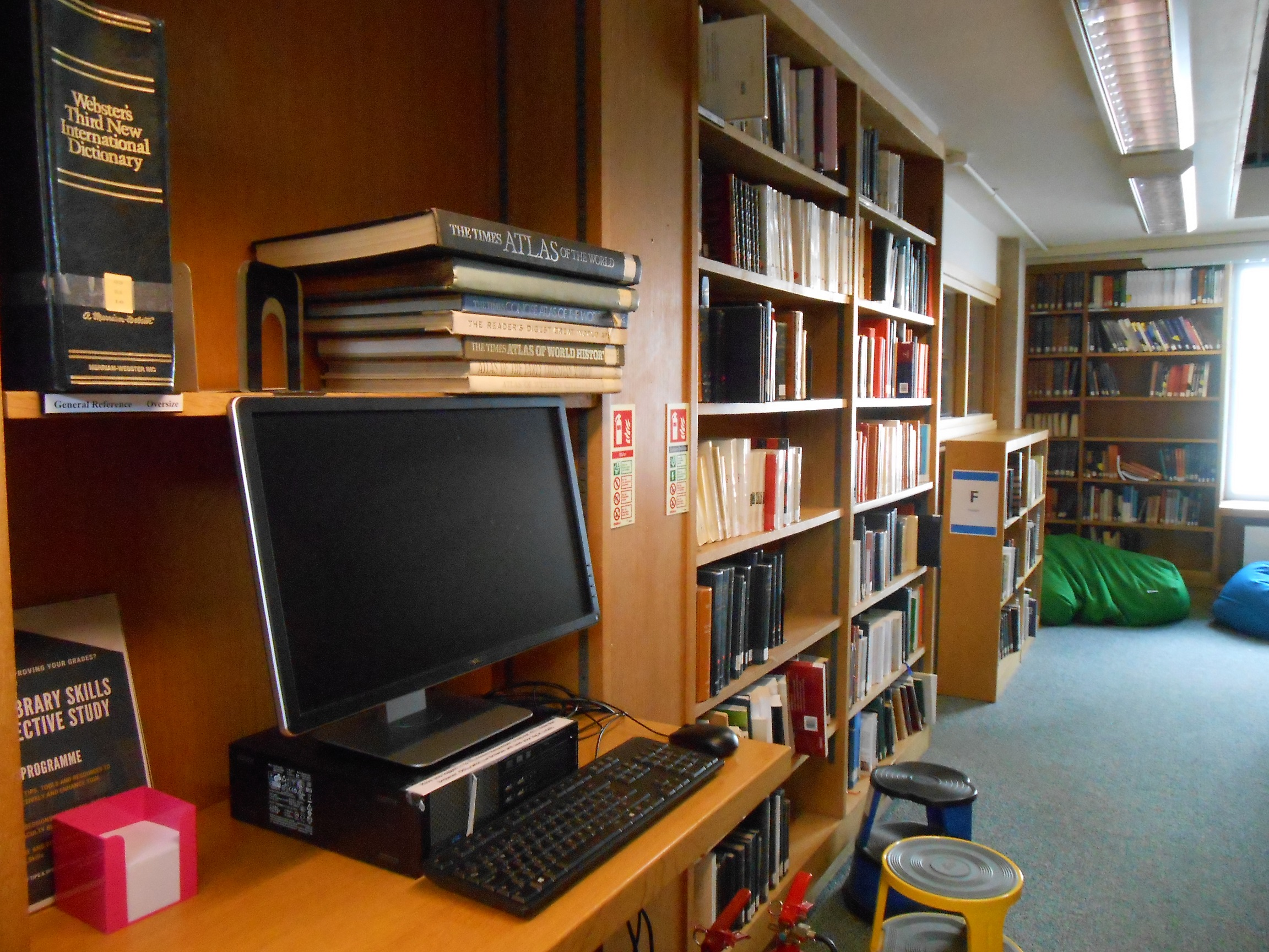 Colour photo of the MMLL Library 1 floor, with an iDiscover catalogue terminal on the foreground