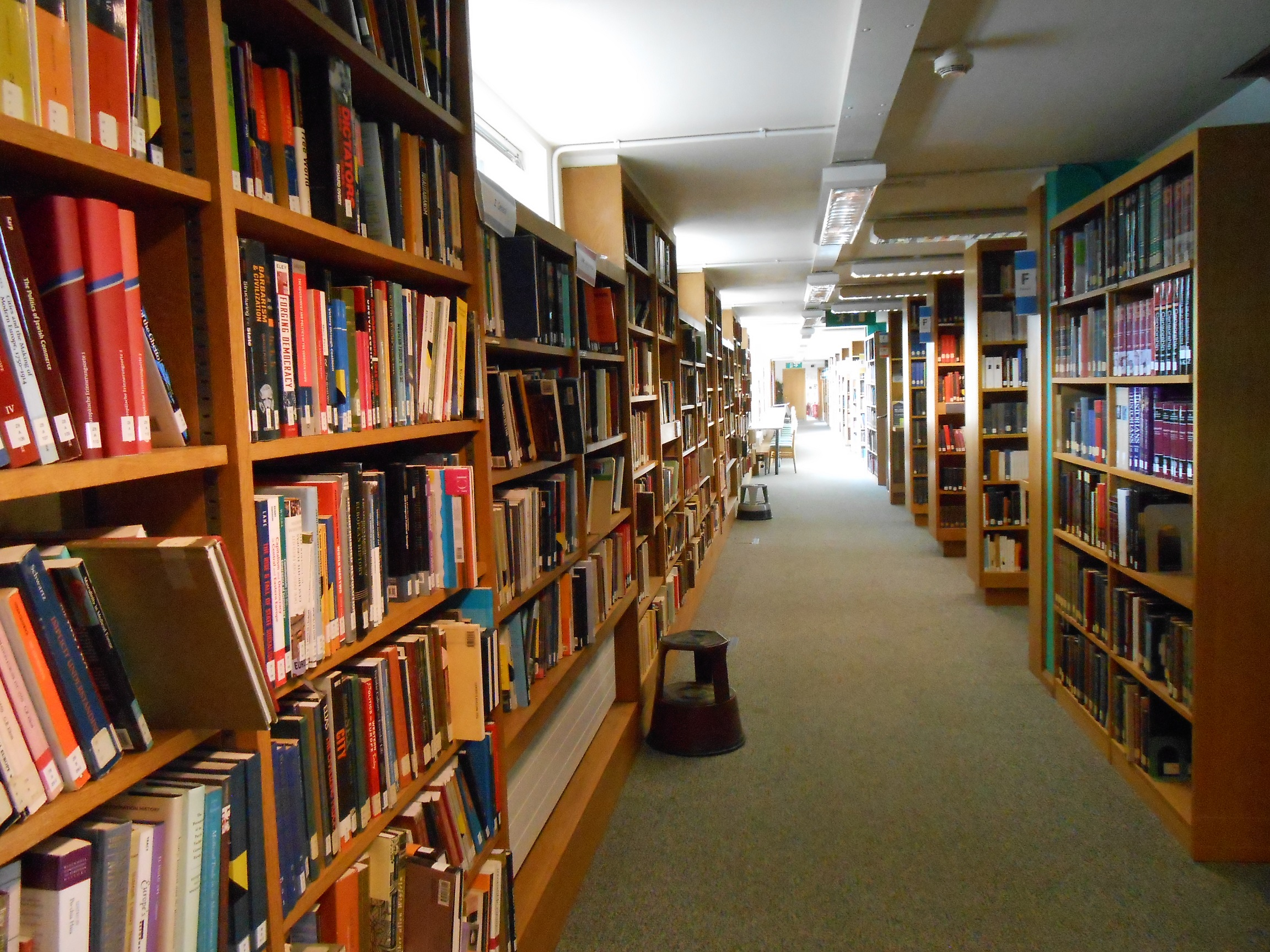 Colour photo of the MMLL Library 1st floor, with rows of shelves down the corridor