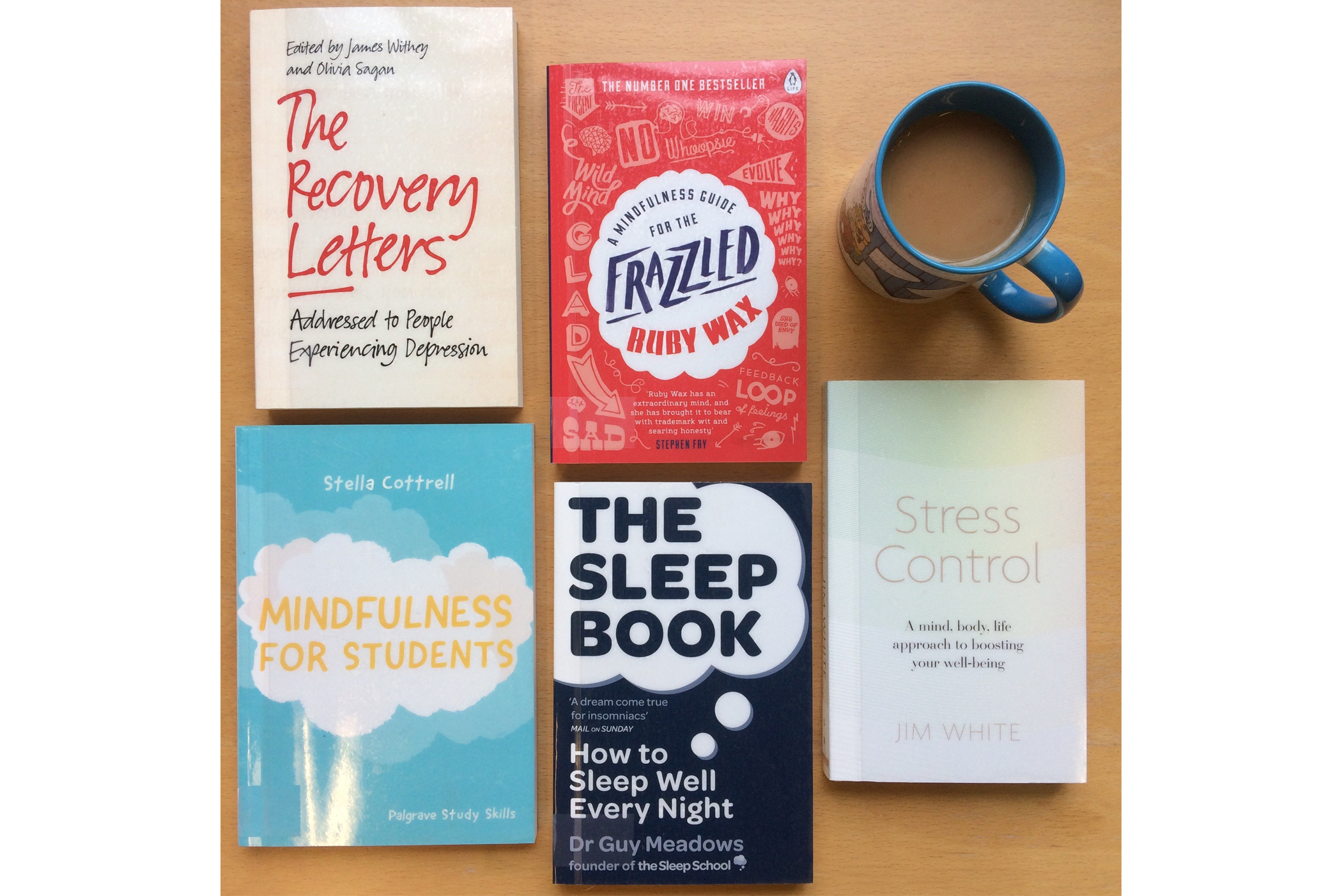Photo of books on wellbeing and a cup with coffee on the table