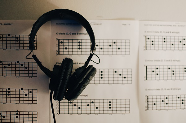 A photograph of some sheet music and a pair of headphones