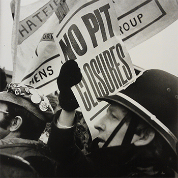 Photograph from the Undermined exhibition showing placards and a policemen.