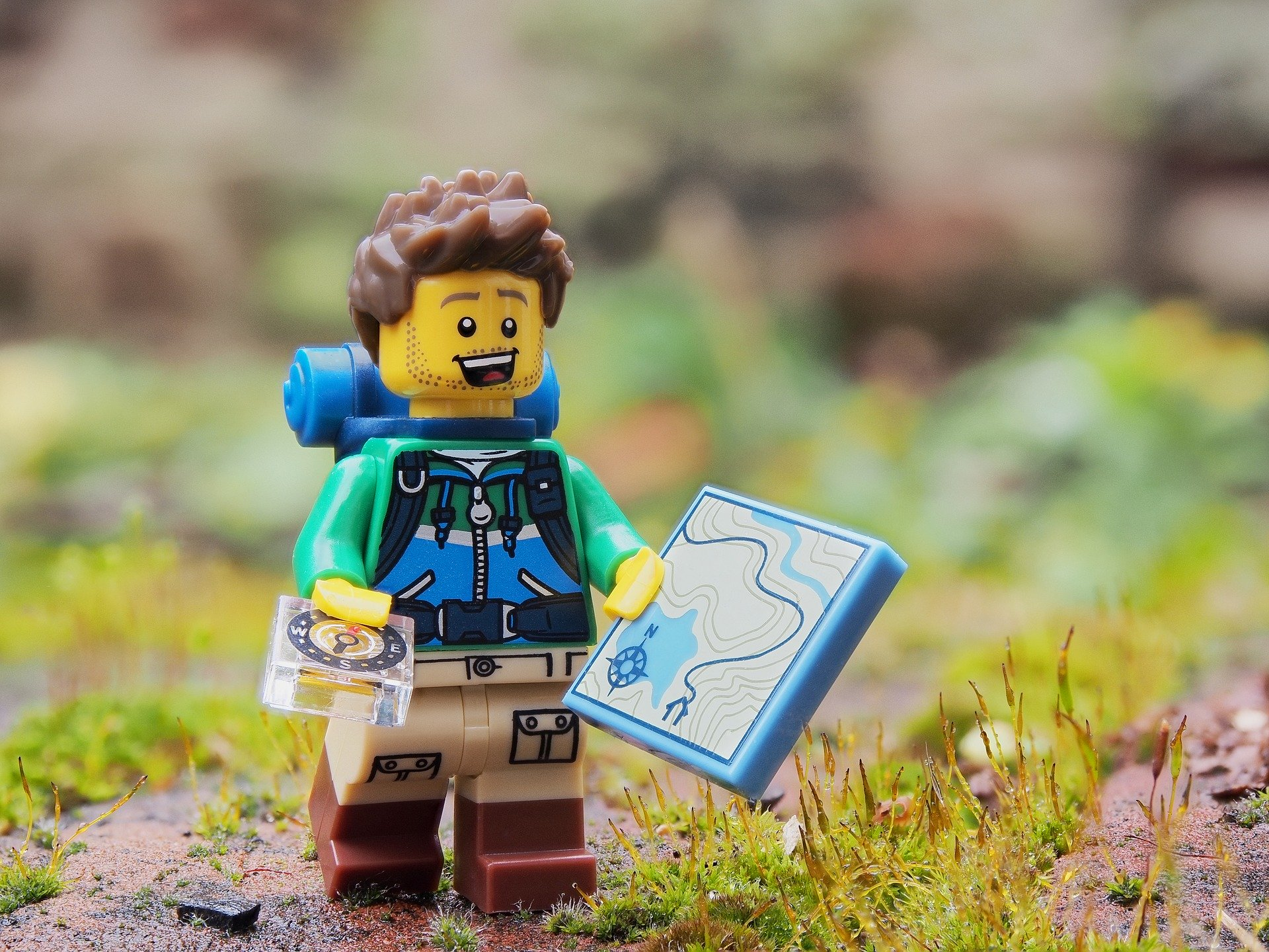 Toy person on some grass and stones, holding a map and a compass