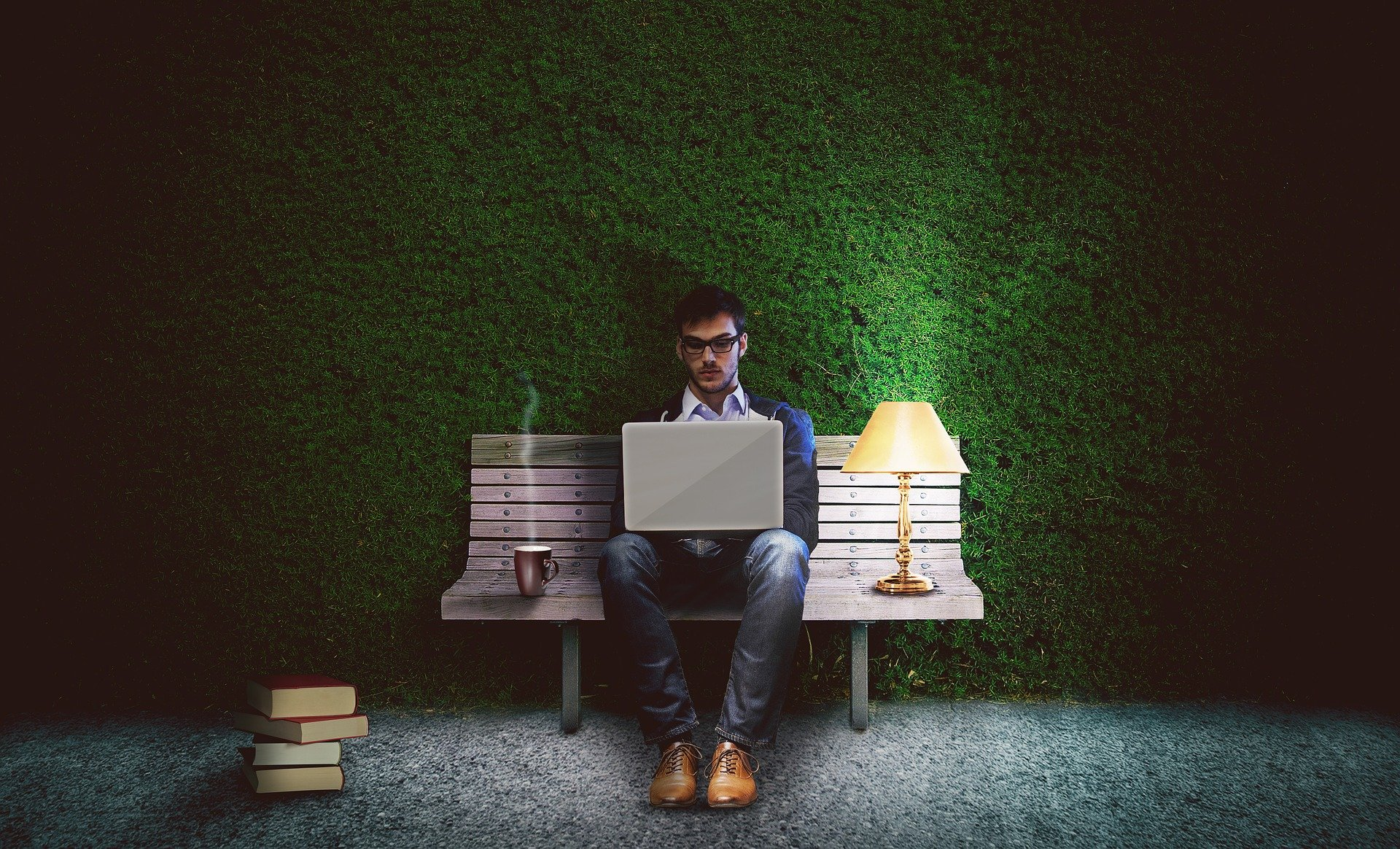 A man sat on a park bench in the dark with a laptop on his knee and a lamp by his side.