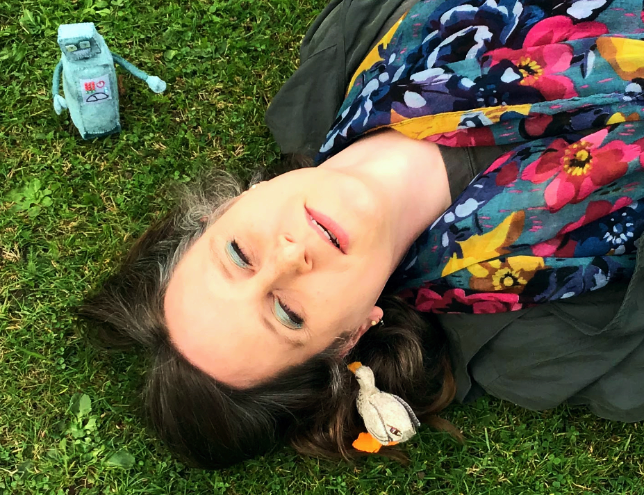 The author, unconscious on the Fairhurst lawn, a tiny duck at her ear, and a small robot watching over her