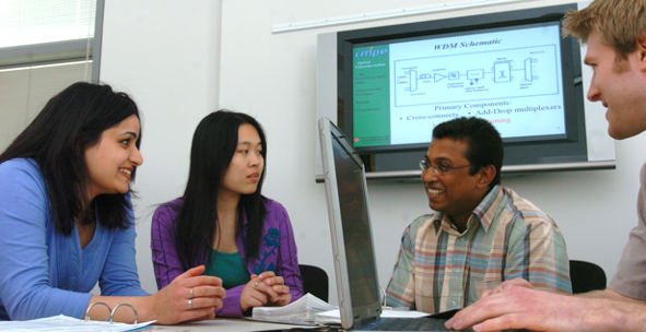 Four people having discussion round table with screen in background showing diagram on slide