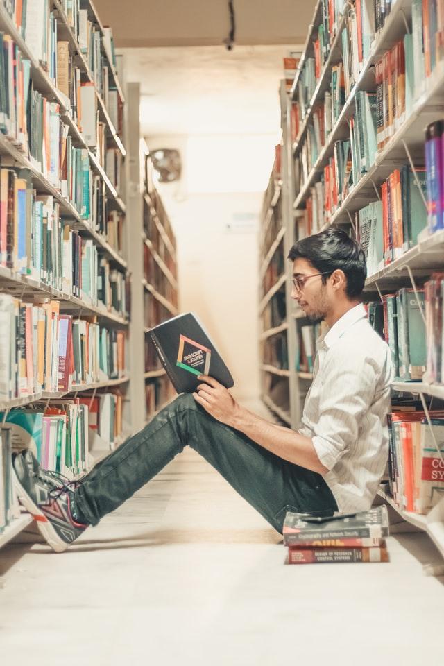 photo d'un jeune homme lisant assis entre deux étagères d'une bibliothèque