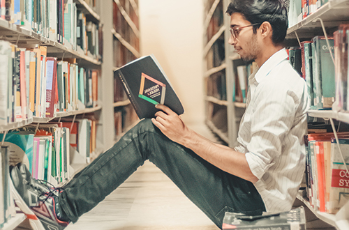 student sitting on the floor reading