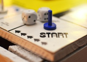 Two dice and a playing piece on a game board showing the work start