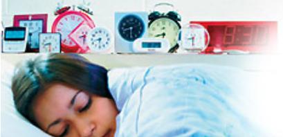girl sleeping surrounded by alarm clocks