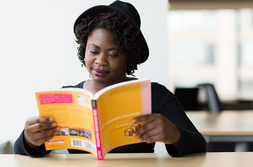 femaie student reading book in the library