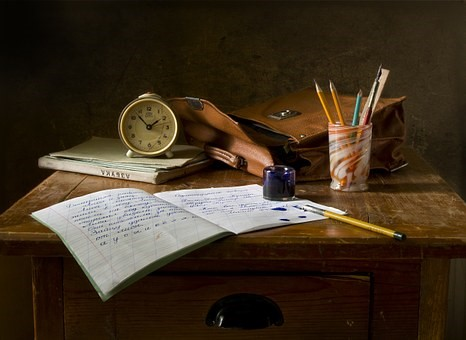 Desk with alarm clock, satchel, pen pot and notebook