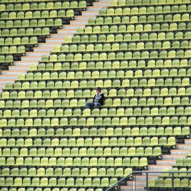 One person sitting in an empty stadium