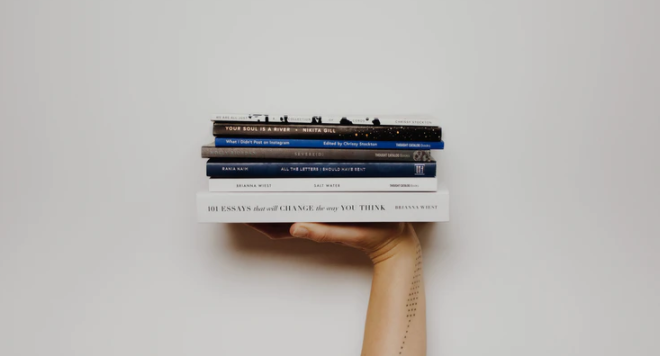 A hand holding a small pile of books aloft