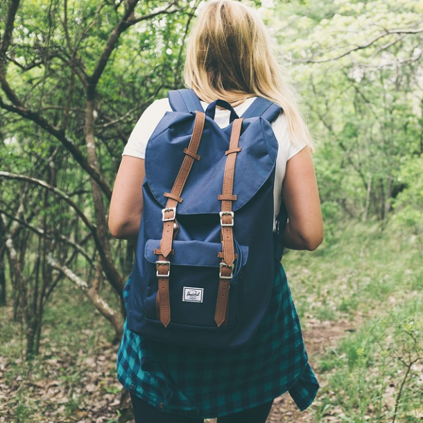 Girl walking through a wood carrying a backpack