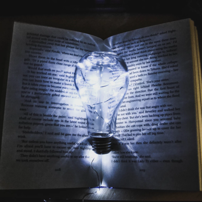 Open book with a glowing light bulb between the pages