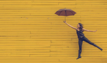 Woman holding an umbrella and flying through the air