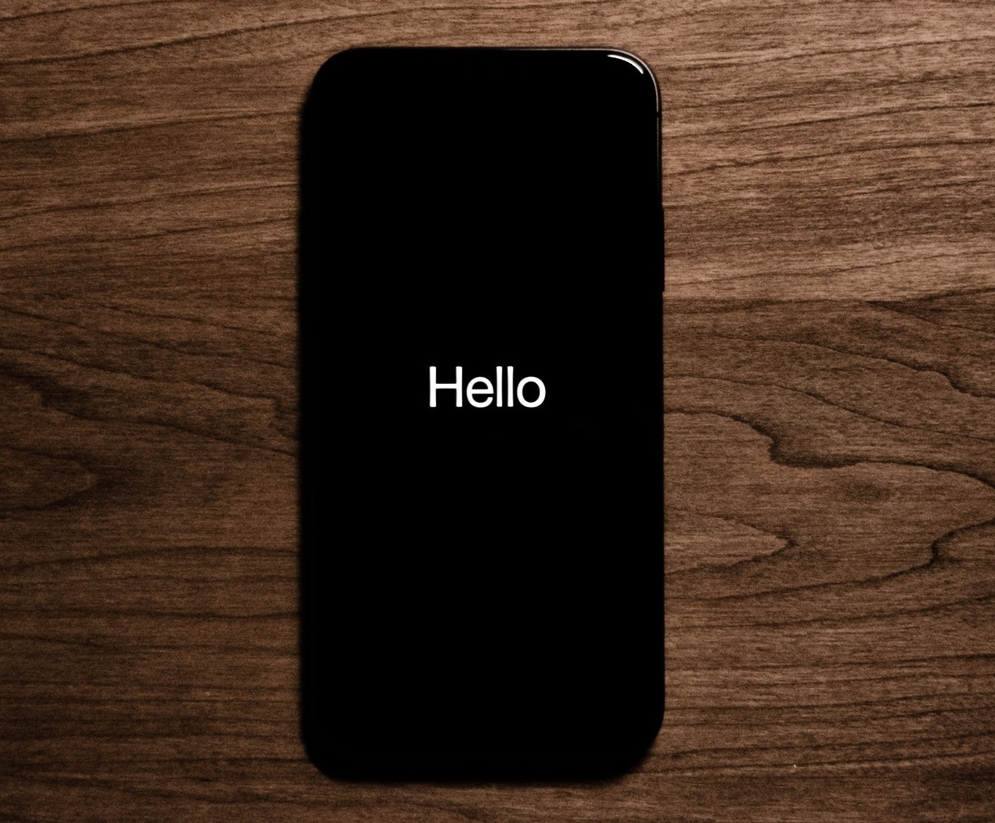 A black iphone on a wooden table displaying the word 'hello' in white letters