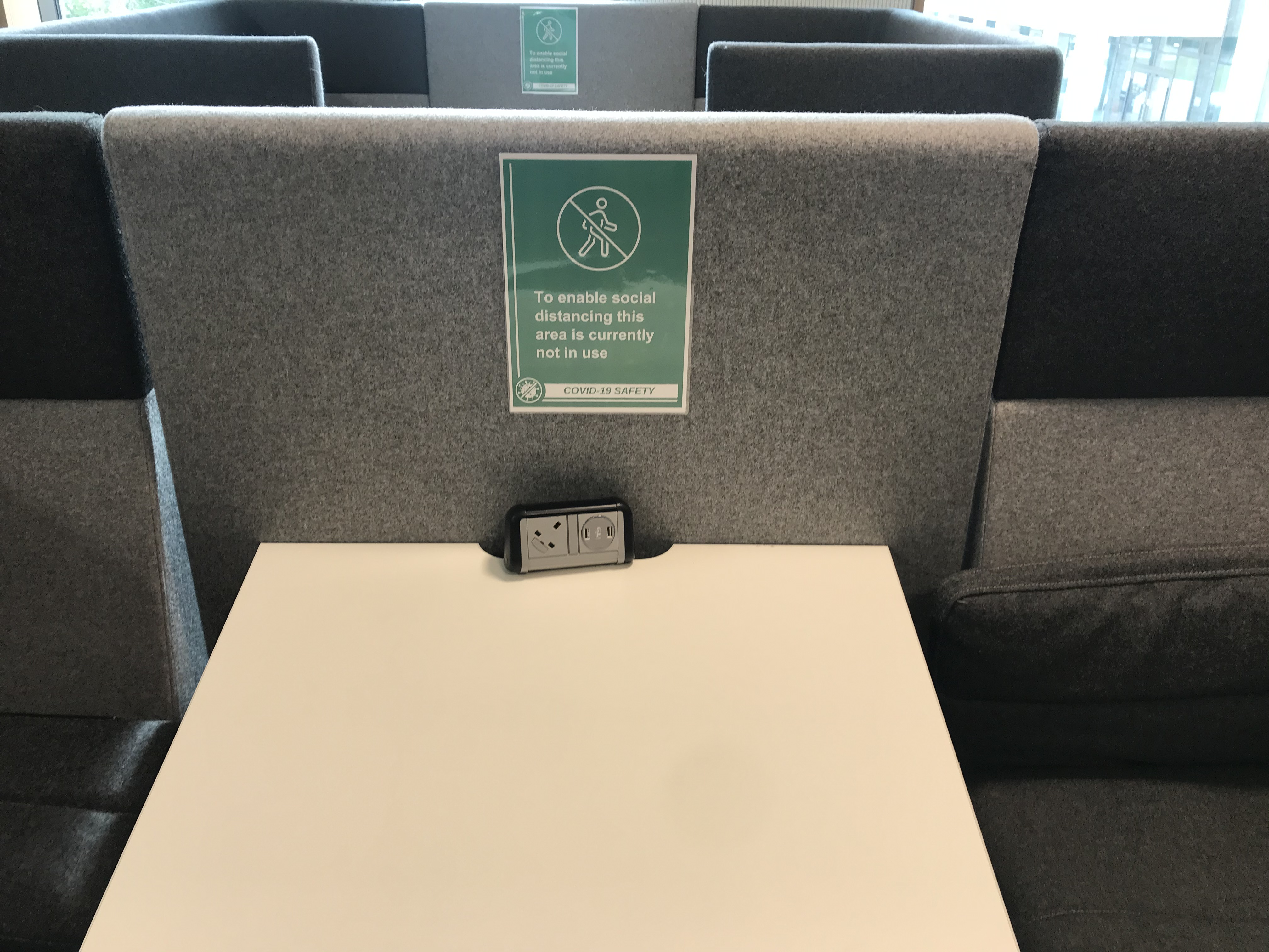 grey study booth with green sign reminding students to socially distance