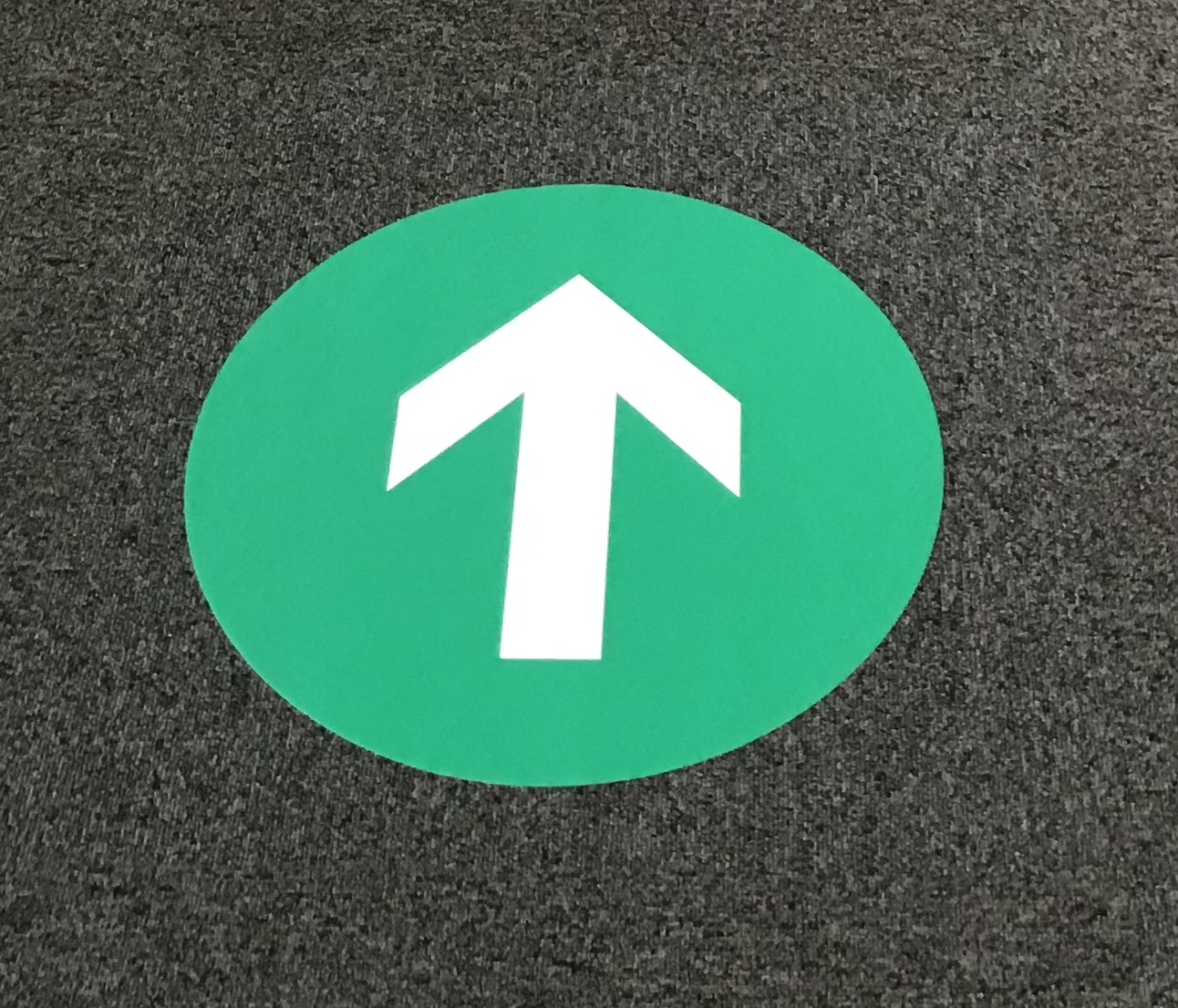 white arrow on a green circle showing the direction of traffic inside the library