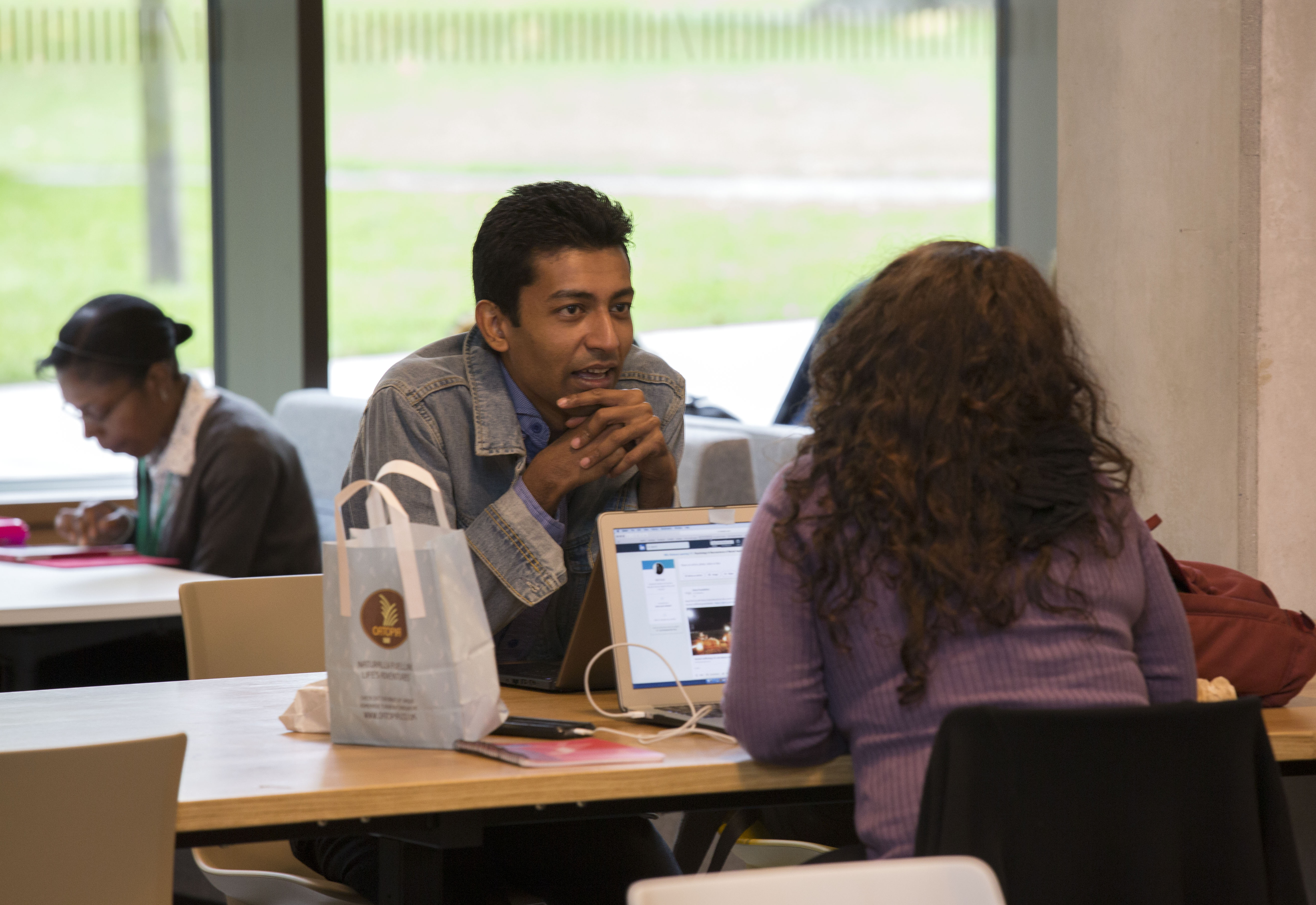 Two individuals studying and eating in the Library cafe