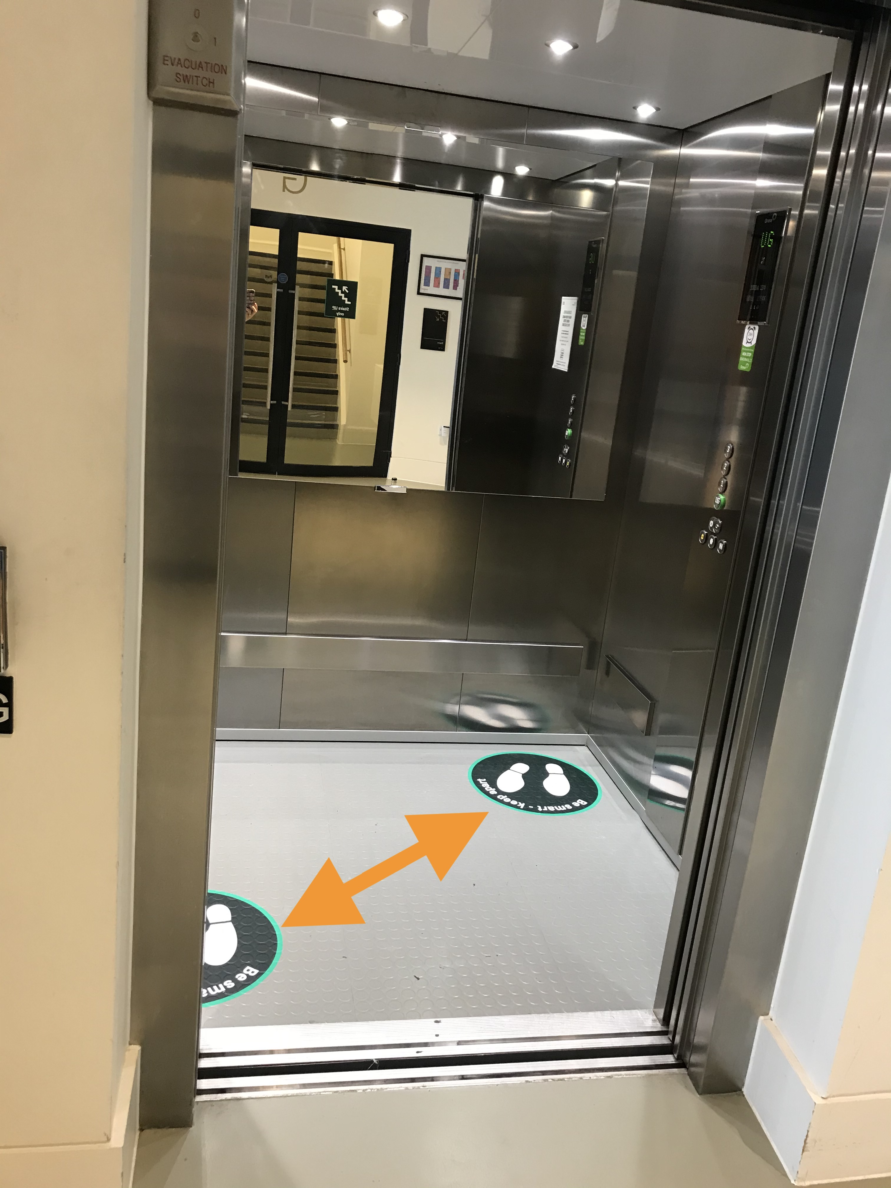 interior of the lift with two floor signs to stand on to show maximum capacity