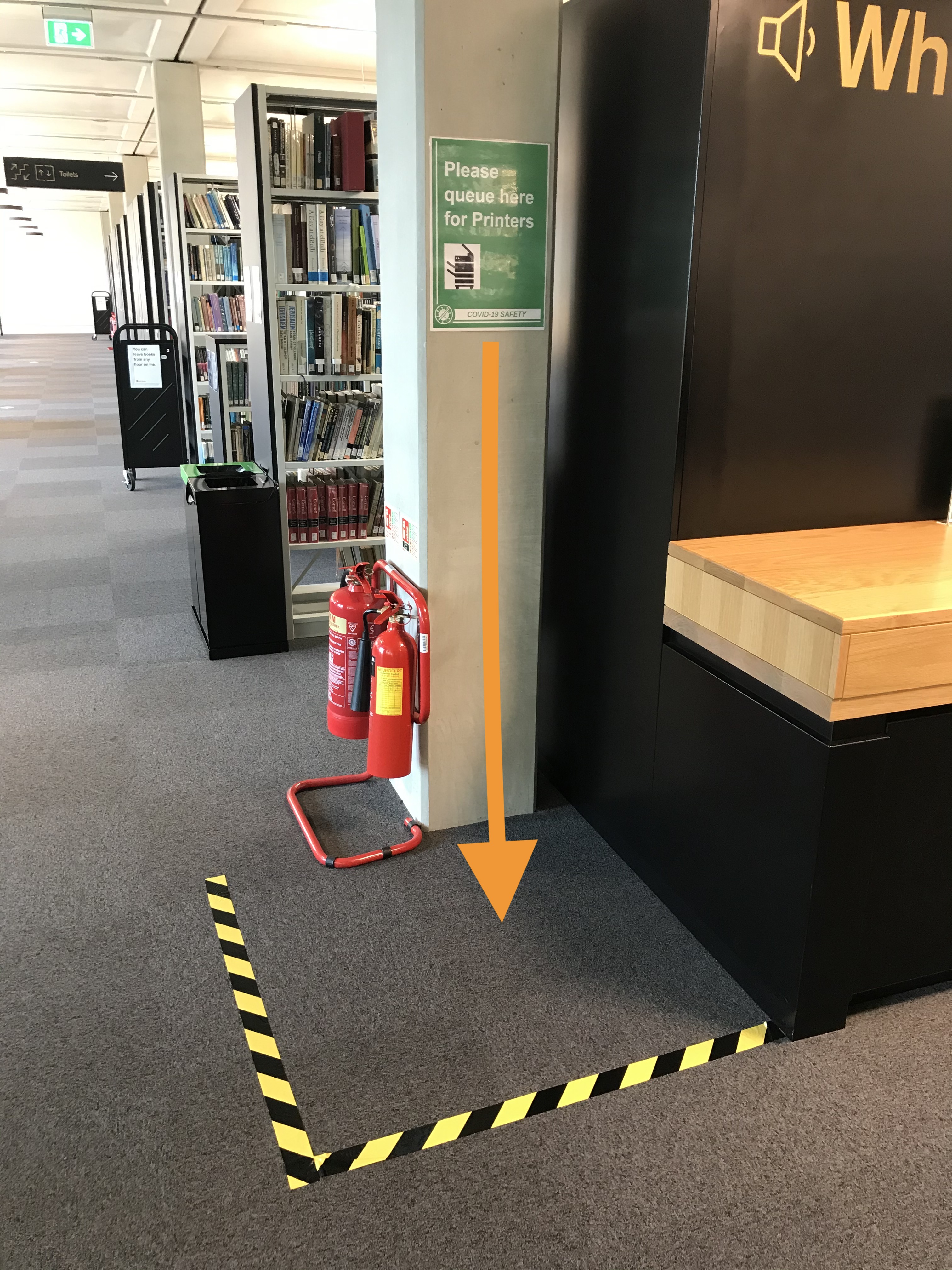 yellow taped section of the floor near the printer to show where to queue